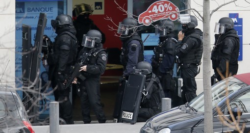 Members of special French RAID forces secure the area next to the post office in Colombes outside Paris, were an armed gunman is holding hostages